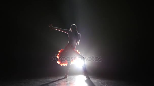 Beautiful girl dancing rumba in the studio on a dark background, smoke, with white backlight