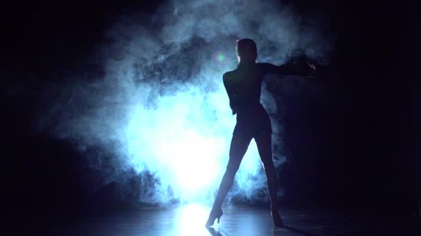 Lady szambát táncol a stúdióban, sziluett. Lassú mozgás