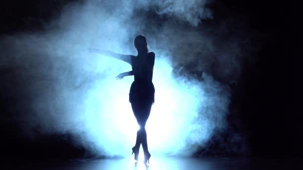 Tanečník provádí latinské tance v studiu silueta. Zpomalený pohyb