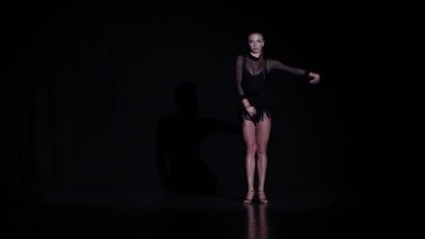 Girl dancing rumba elements in the studio, black background. Slow motion