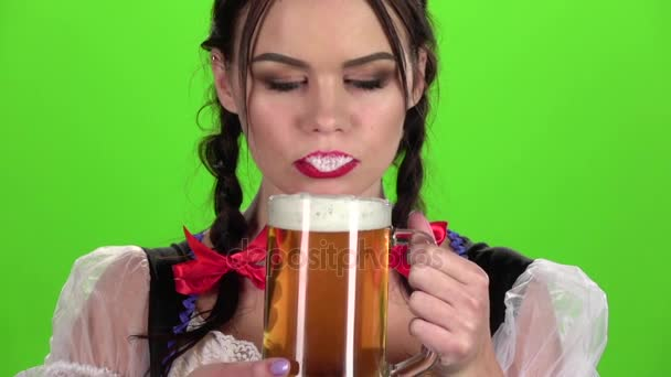 Oktoberfest lány, flörtölés, és egy üveg sört. Zöld képernyő. Lassú mozgás