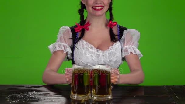 Mädchen in bayrischer Tracht bricht Gläser mit Bier. Green-Screen. Slow-motion