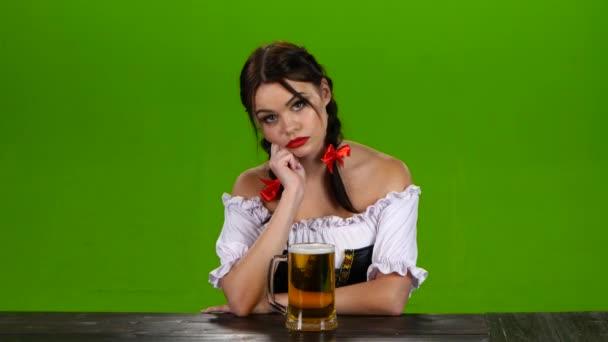 Mädchen in bayrischer Tracht mit Getränke Bier am Tisch sitzen. Green-screen