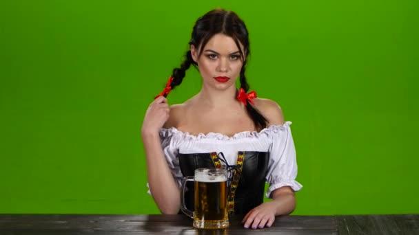 Mädchen in bayrischer Tracht feiert Oktoberfest Biertrinker und winkt. Green-screen