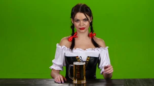 Girl bietet leckeres Bier auf dem Oktoberfest zu versuchen. Green-screen