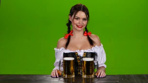 Lady v bavorské kostým nabízí vypijte dvě sklenice piva. Zelená obrazovka