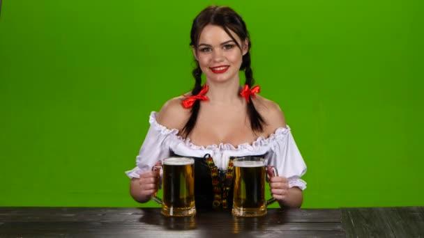 Lady in bayrischer Tracht bietet zwei Gläser Bier trinken. Green-screen