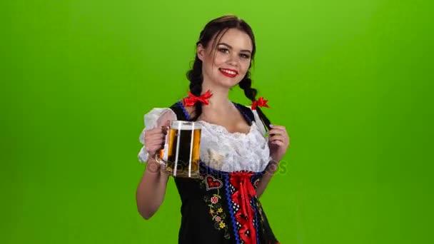 Frau in bayrischer Tracht tanzt mit einem Glas Bier in der Pickup. Green-screen