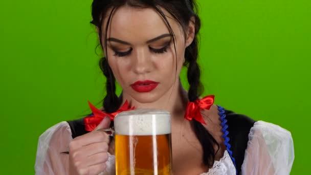 Hravá dívka foukání sklenici piva a úsměvy. Zelená obrazovka