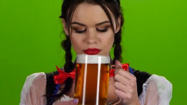 Oktoberfest girl flirting and drinking beer from a glass. Green screen