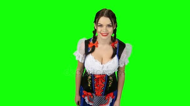 Dívka v bavorském kroji ukazuje palcem. Zelená obrazovka. Pohled shora