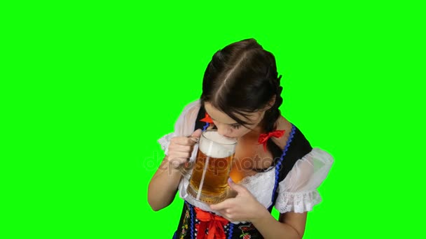Girl in national Bavarian costume drinking a beer. Green screen