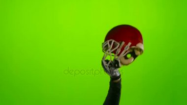 Football players hand lifts the helmet. Green screen. Slow motion