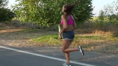 Gyönyörű lány jogging egy ország közúti reggel. Lassú mozgás