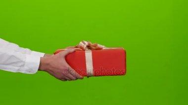 Ajándék, ami mans kezében. Oldalnézet. Közelről