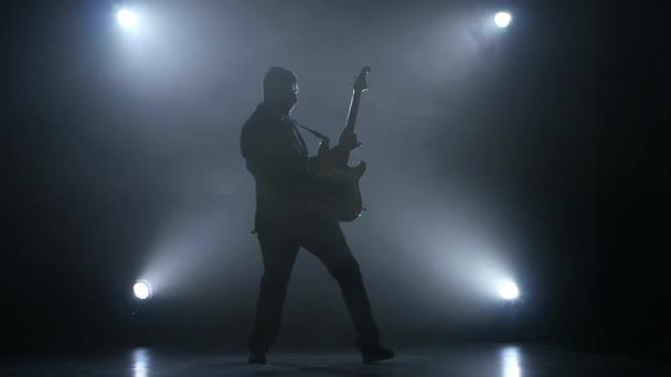 Hudebník virtuos brnknout do strun na basovou kytaru. Zpomalený pohyb