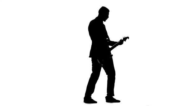 Hudebník trhat na elektrickou kytaru struny. Silueta