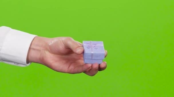Dárek v malé krabičce, které dávají muži ruku