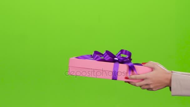 Dárková krabice. Dívka dává muži růžová pole. Detailní záběr