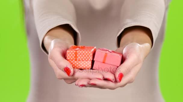 Két ajándék doboz a kezében a nők. Közelről