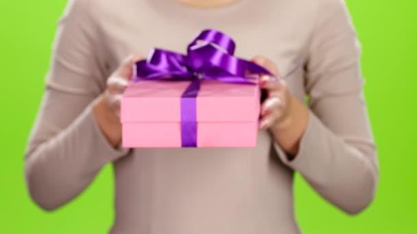 Mädchen hält eine Schachtel mit einem Geschenk in die Höhe. Studio