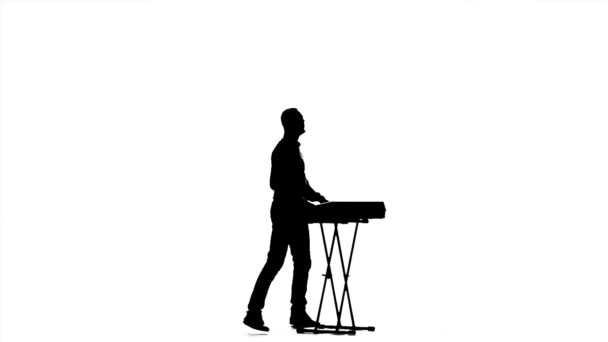 Man playing on a synthesizer. Jumps to the music ...