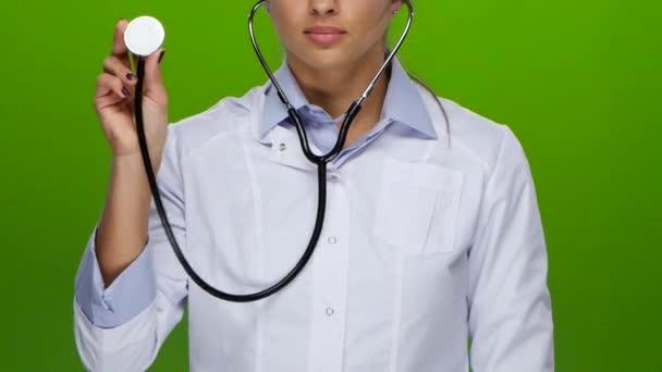 Doktor dívka poslouchá stetoskopem, oblečený v bílé lékařské šaty a tričko, na prstech elegantní manikúru, vážné koncentrované dopředu vidět v půl, do pasu, zelená obrazovka