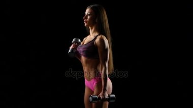 beautiful strong woman exercises with dumbbells