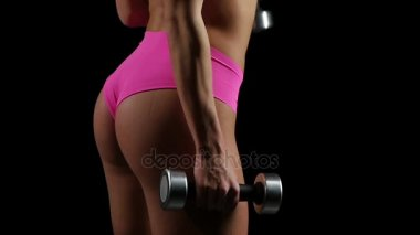 Beautiful fitness woman with lifting dumbbells . Sporty woman lifting light weights. Fit girl exercising building muscles. Slow motion.
