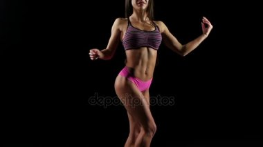 Young sporty woman posing against in bikini on black. Slow motion.