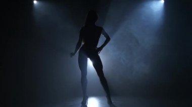 Silhouette bodybuilding girl posing in studio.