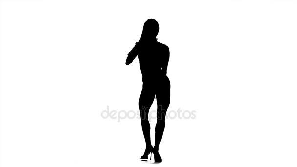 Silueta kulturistika dívka pózuje na bílém pozadí v černé a bílé. Zpomalený pohyb.