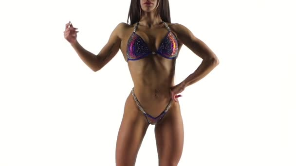 Štíhlá žena kulturista lodě v bikini fitness soutěže na bílém. Zblízka. Zpomalený pohyb.