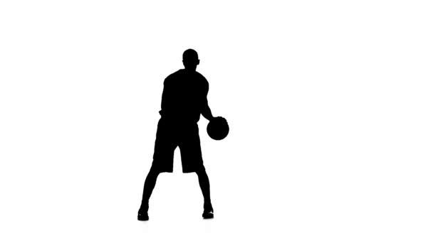 Basketball feint passes the ball. Silhouette. Slow motion. White background.
