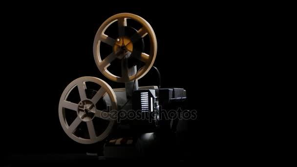 Retro projector showing film. Studio black background
