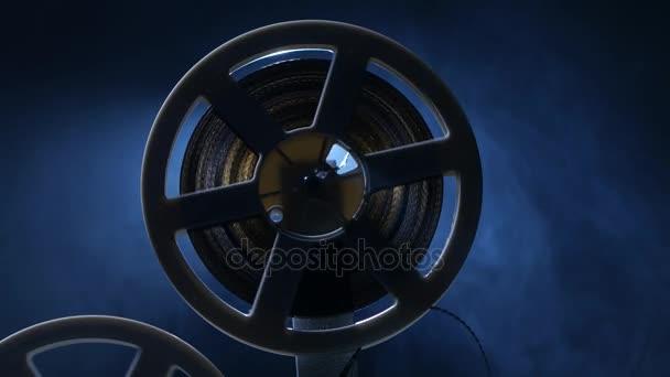 Film rá egy tekercs projektor tekertek. Sötét háttér, háttérvilágítással