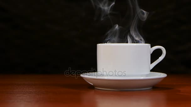 Cup of coffee costs on a wooden table and spreads a pleasant smell