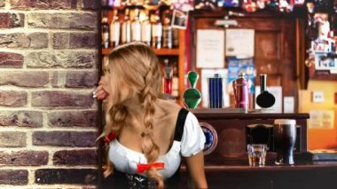 Young sexy Oktoberfest woman wearing a traditional Bavarian dress in the brasserie looks out from behind a wooden wall