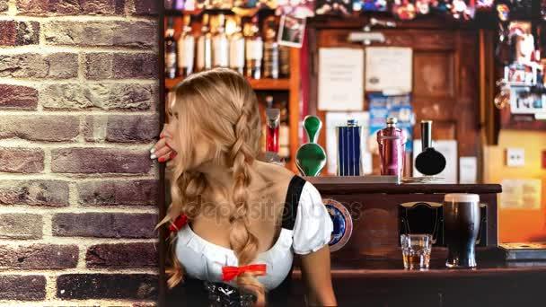 Fiatal szexi Oktoberfest nő, fárasztó egy hagyományos bajor ruha söröző úgy néz ki, egy fából készült fal mögül