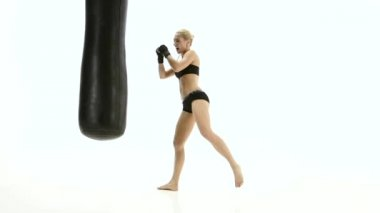 Woman kickboxer with passion warming up with a punching bag