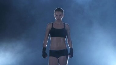 Sportswoman boxer warms up the muscles before the fight