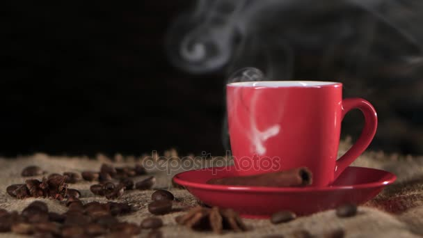 Šálek horké kávy šíří příjemnou vůni v místnosti. Černé pozadí
