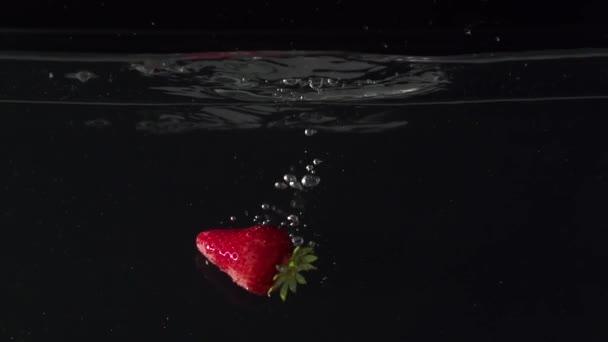 Dva strawberryes kapka do vody v slowmotion