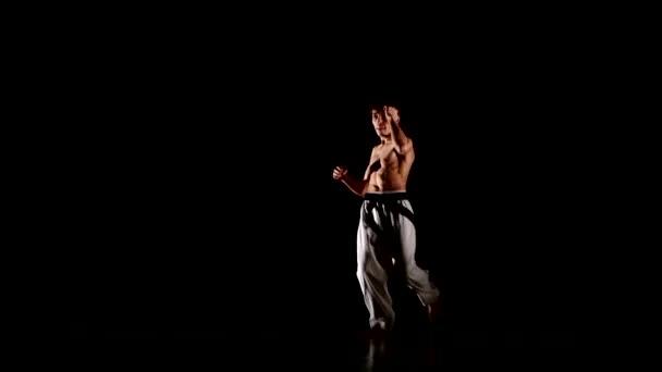 mladý muž karate nebo taekwondo, skákání, high kick a pěst děrování izolovaná na černém pozadí