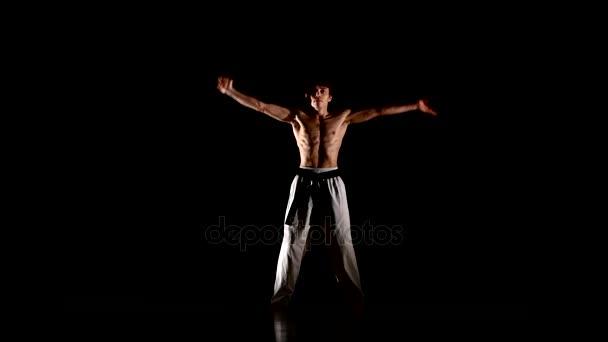 Mann trainiert Karate oder Taekwondo isoliert auf schwarzem Hintergrund