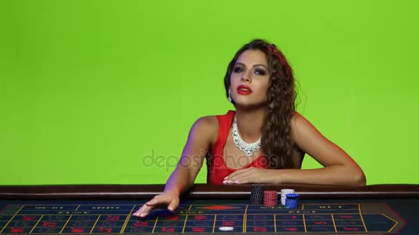 Bella ragazza che si siede al tavolo da poker in un casinò