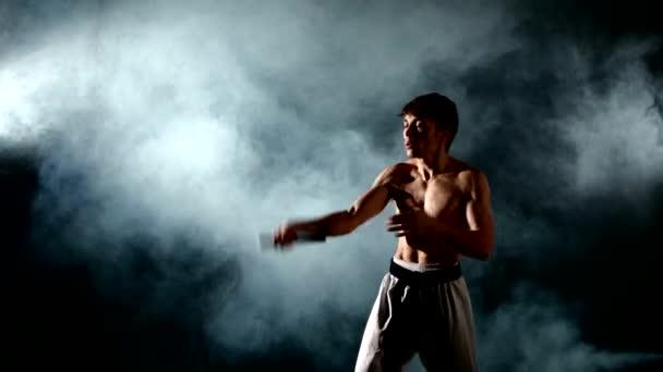 férfi gyakorló karate vagy kung fu. Mester gazdaság nunchuck. Közelről
