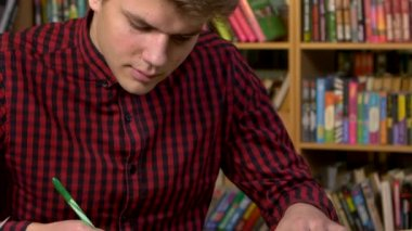Student using his digital tablet in a library, preparing for Abstracts. Close up