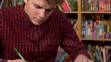 Student pomocí digitální tablet v knihovně, příprava na abstrakty. Detailní záběr