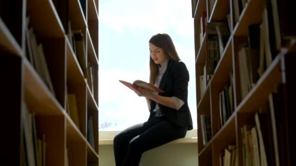 studentky čtení knihy na okenní parapet v knihovně. Detailní záběr
